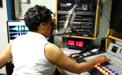 woman working a sound board in the MC radio station