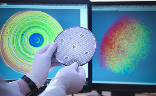 Scientist working with silicon wafer in laboratory