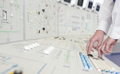 technician's hands at nuclear reactor control board