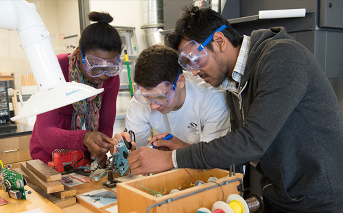 Engineering students work together on a circuit board