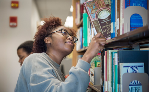student in library taking down book