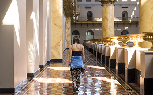 photo of woman walking through marble hallway