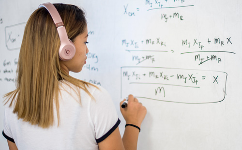 student at white board working on a math problem