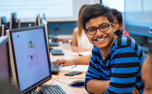 Student smiling while working at computer
