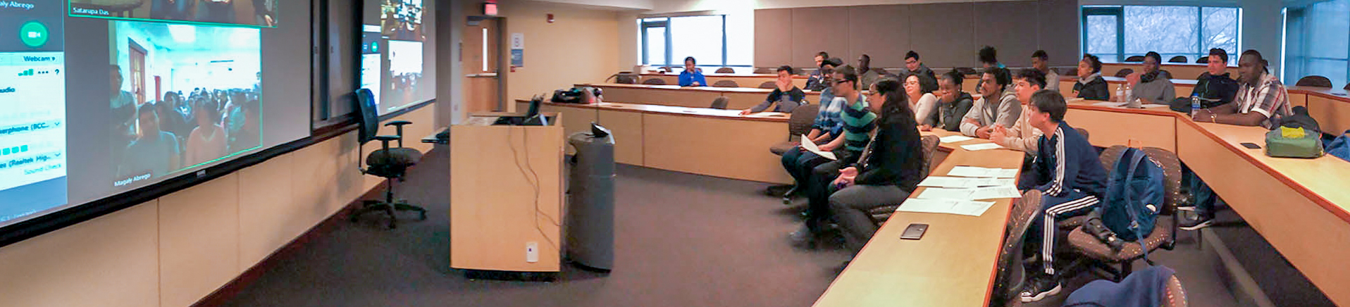 Students in a classroom looking at a video chat